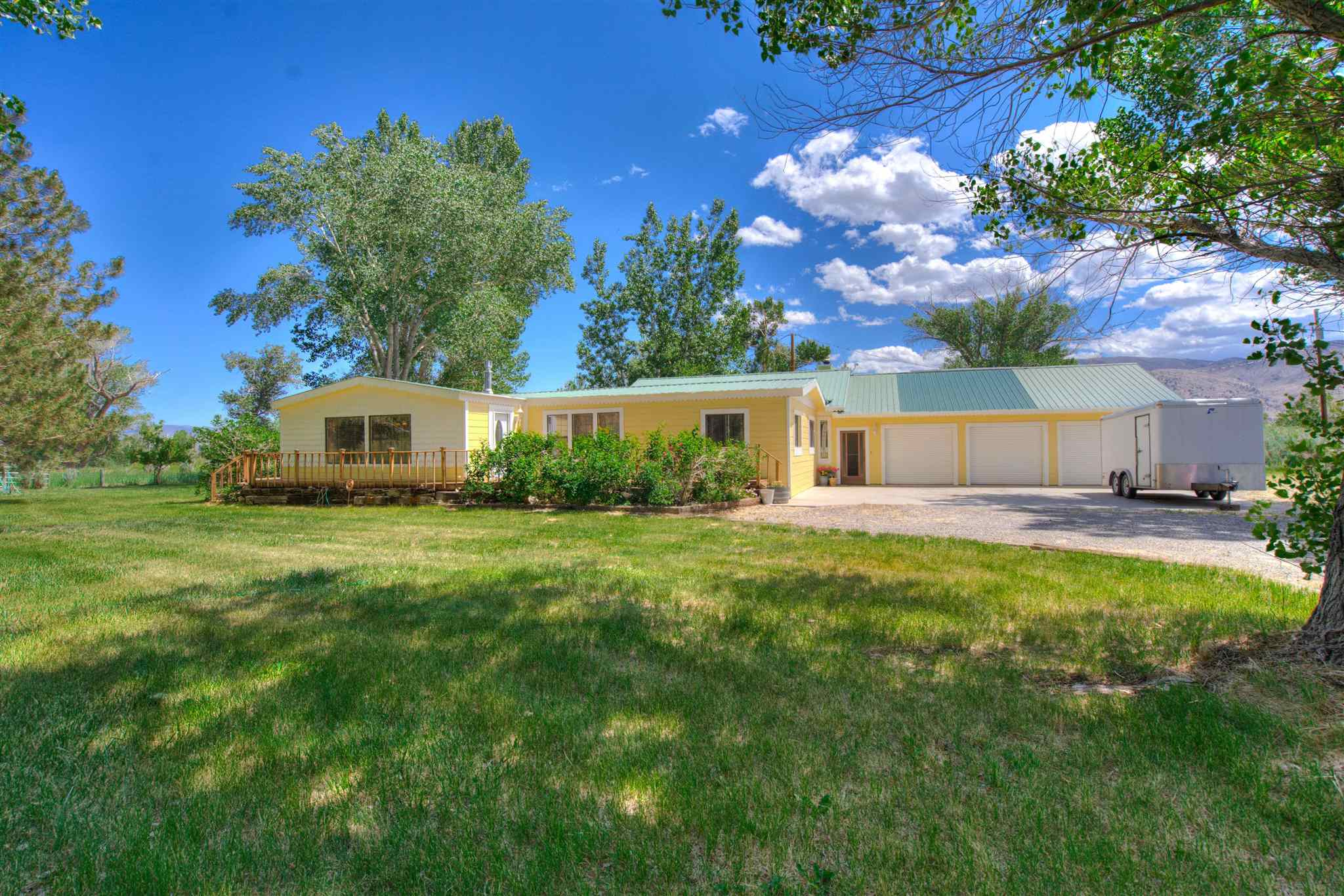 Stunning Ranch and Riverfront Property! Beautiful 3 bd, 2 ba home, 3 car attached garage, an mans dream workshop (32x36),  barn, fenced and cross fenced pasture and river frontage.  The home features an oversize custom Italian theme gourmet kitchen with large island and bar to gather around while entertaining.  The kitchen has a separate wall featuring a coffee/snack bar area and all counters are gorgeous granite and finishes. 2 refrigerators. washer and dryer are included.  Custom Hardwood cabinetry with pantry, spice shelves, and many special details. Adjacent Informal dining area has a gas log fireplace and a full wall Wine Bar and cabinetry.   You will also find a large formal dining room with views of the ranch and lovely faux copper ceilings add to the ambiance.  The features a well designed Victorian living room, with picture windows and treatments and a separate entry hall.  In addition to the living room, this home has a country family room (800 s.f.)  with gorgeous rock wall and wood stove. The entertainment center stays with the home.  This lovely space could be your    office and game room, hobby room, or man cave.  The home has custom touches of wall paper, chair rail, crown molding, pine wood ceilings  The Master Bedroom features custom wall paper and chandelier, double French doors leading to the front /side deck where you can enjoy your morning coffee and take in the fresh mountain air.  Also features a walk in closet with special shelving.  The Master bath features a gorgeous Victorian pedestal tub and enclosed powder room.  This home has many details and design that is so hard to find.   The pride of ownership shows.     Exterior of home has just been repainted.   On the 5.45 acre ranch is fenced and cross fenced, has a barn and a special garden area full of roses, peonies and also a Gazebo. Great place to relax in the afternoon.  This home is a must see and a rare find.