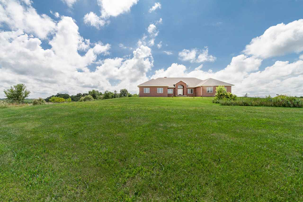 Enjoy verdant pastoral views of rolling farm land from this spacious and luxurious all brick ranch on 39.9 acres. All the living spaces and main level owner's suite feature walls of windows that make the most of the spectacular country views, including the kitchen, sunroom, den with fireplace, and formal dining room. A wraparound deck with two tiers can be accessed from the owner's suite, living room and sunroom. An expansive, unfinished, lower level walkout includes a floor-to-ceiling brick fireplace and offers an incredible opportunity to make the space your own. 3-car garage.