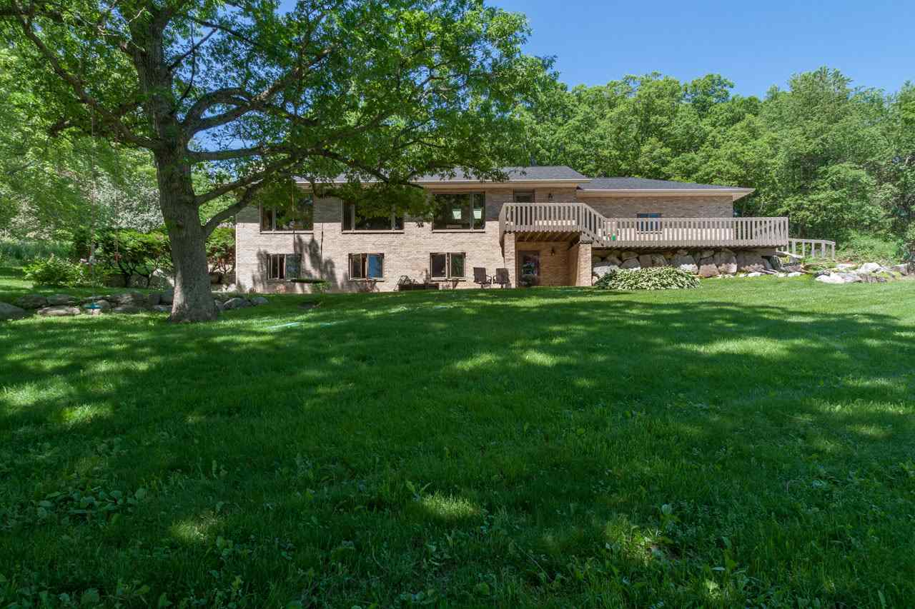 Executive estate with large shed and barn set on 20 acres just minutes from Madison. Extensively remodeled in 2014. Enjoy  over 1500 sq ft. of great room with stunning nature views. New hardwood floors, fireplace and kitchen featuring solid pecan cabinets. Main floor Master Suite w/Brazilian cherry floors (patio is hot tub ready) & 2 cedar lined closets, as well as 3 add'l bdrms on lower level. 3 outbuildings include wrksp w/furnace and LP hookup, storage shed w/skylights, & a 12x12 shed for storage. 20 acre maintained for walking/skiing.  Black Walnut, White Oak, apple & various fruit trees. Plenty of Wildlife too!