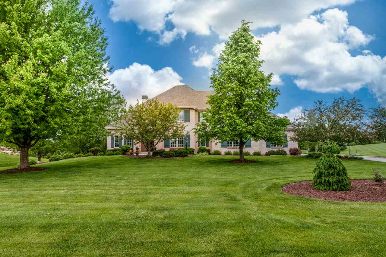 This stately brick faced home on over 1.5 acres in Pheasant Point exudes European elegance. A double arched entry door, sunny office w/floor-to-ceiling bookshelves & french doors w/transom, a gorgeous open staircase w/wrought iron balusters, a stunning great room with a wall of windows that flood the space w/natural light and highlight architectural details like the arched built-ins flanking the  gas fireplace with its graceful mantel. The open kitchen + dinette, refined in its design, has all the modern luxuries you want in a kitchen. You'll also love the exposed finished lower level rec room w/fireplace, large studio/exercise rm, office & bedroom. The upper level bedrooms include a tranquil owner's suite + 2 other large bedrooms with fantastic built-ins. So much to love!