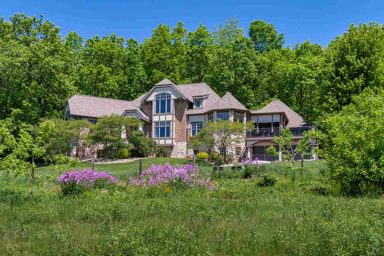 One of a kind ~13 acre oasis in Verona, just 20 min to downtown Madison. Nestled on a wooded hillside overlooking prairie and farmland to the South and West and forest North and East, this beautifully crafted home was updated in 2019 to the highest standards. ML includes a great rm w/wet bar & fp, fml DR, den opening to patio, waterfalls, & koi pond, eat-in kitchen w/Wolf, Subzero,new laundry rm, 2 new Brazilian Walnut decks, scrn porch, & luxurious master suite w/new spa bath/steam shower. Walkout LL features family room w/fp, kitchenette w/bar, 500+ bottle wine room, billiards rm, theater rm, office & ensuite BR. Two ensuite bdrms on UL w/remodeled baths & 2nd laundry. Two finished 2-car garages for car lovers. Soaring windows, views for miles, turkeys, deer, amazing birds!