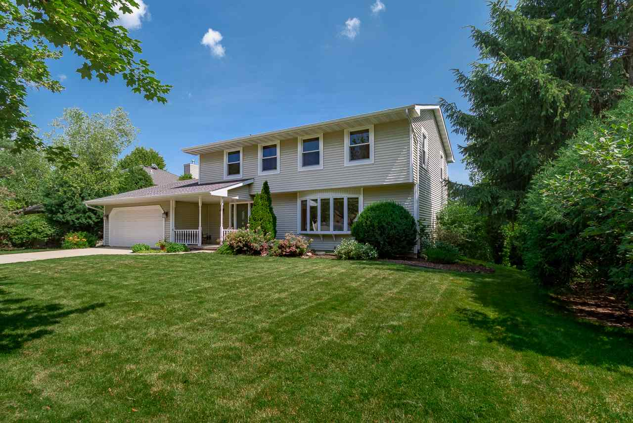 This beautiful Sauk Creek Colonial exudes serenity thanks to its light-filled interior and private outdoor spaces including a large deck that overlooks the private yard filled w/lovely gardens & a patio. A spacious foyer welcomes you into the home where you'll notice the gleaming wood floors that lead you into the sunny living room on the right, which in turn opens to the formal dining room. A few steps further and you're in the open space that includes the remodeled, Prairie-style kitchen with granite counters, pantry, + breakfast bar, the dinette, and the great room w/ a fireplace & doors to the deck. The large, finished LL is bathed in light from the glass patio doors and includes a bedroom & bonus room, perfect for an office or exercise room. Walk to parks, shops, dining & the library!