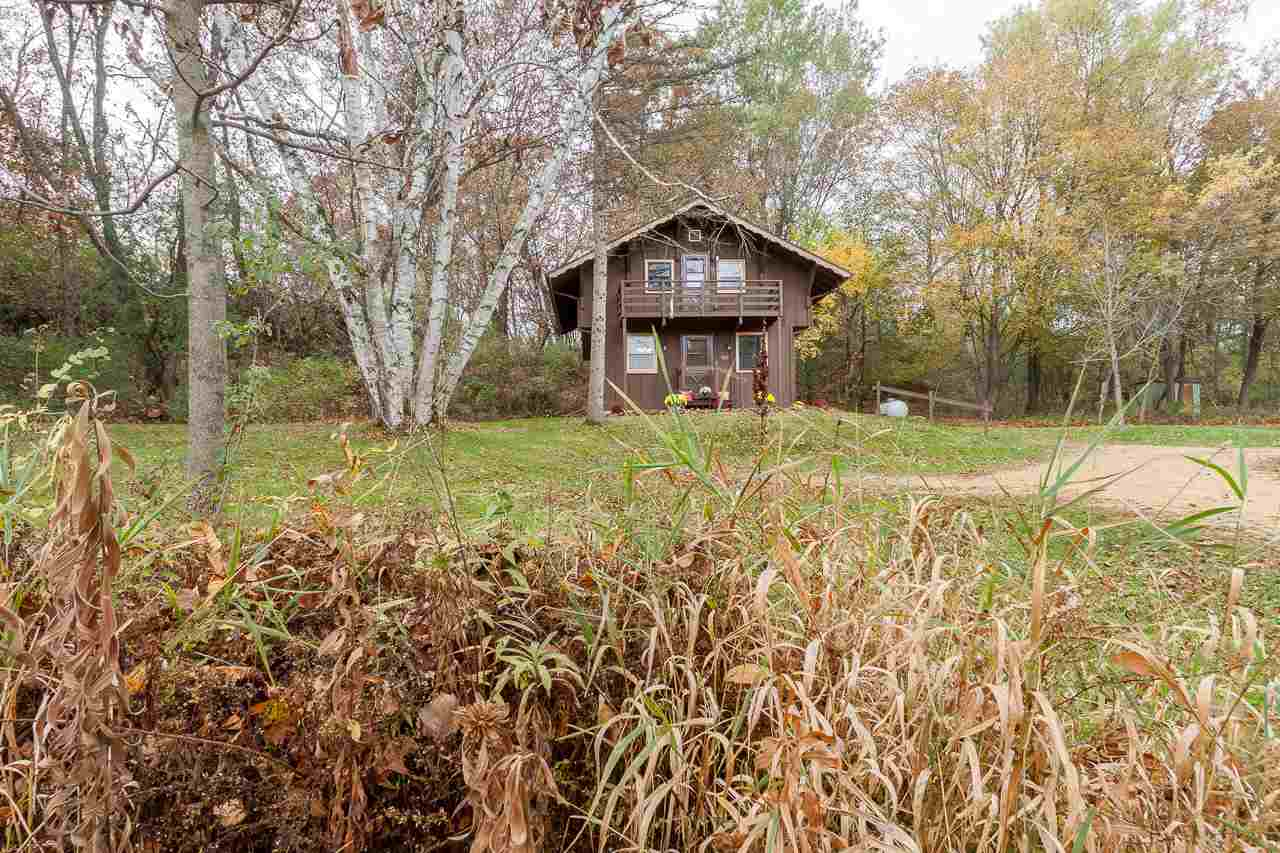 Looking for a country escape? A place to surround yourself with nature and still be close to all the city has to offer? It's your lucky day! This cozy home on almost 7.5 acres on the outskirts of Verona has been completely updated. Reminiscent of a Swiss chalet, the charm of this home cannot be denied. An open layout on the main floor includes the eat-in kitchen and living room, an office or bedroom, and a full bath. Upstairs, the main bedroom features a sitting area, bath with soaking tub, and a separate space that can be a second bedroom or closet. and there are not one, but two decks overlooking the gorgeous wooded lot. If you're looking for land to build your dream home, there's a perfect spot perched on the hill with beautiful views. Enjoy walking trails, wildlife and serenity.