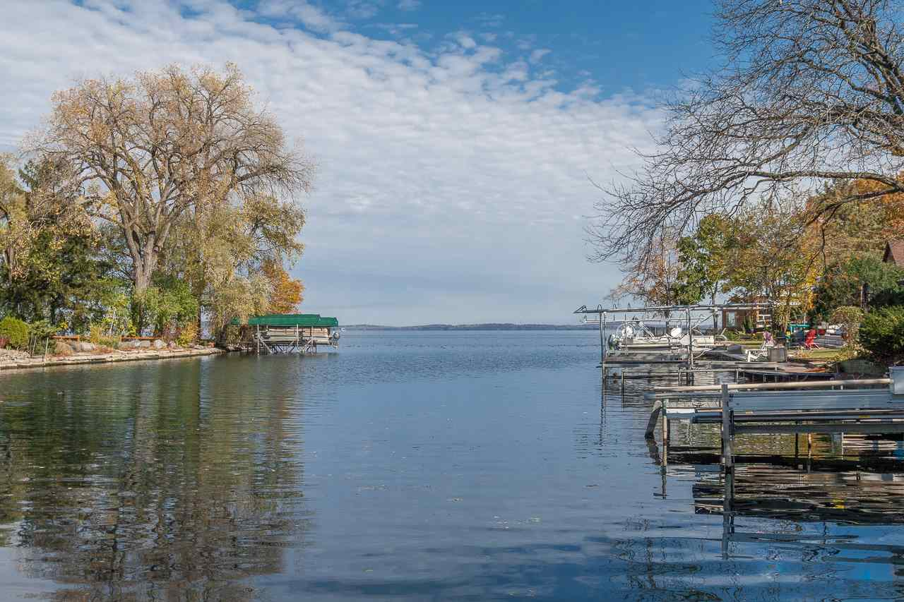 Welcome to the most charming cottage on Lake Mendota. Cherished by one family for 95 years, it's now your turn to create treasured memories in this sweet home.  With 75 feet of frontage complete with a dock + boat lift, it's an ideal weekend getaway, a cozy year-round cottage, or a prime spot to build the lake home of your dreams. Delightful details inside the home include cool vintage appliances—that still work!—original art deco light fixtures, an arched doorway, beautiful wood floors, the cutest bathroom you've ever seen, and, best of all, an expansive 3-season porch overlooking the water that you will never want to leave. Everything you need is on one floor— the spacious kitchen, sunny living/dining room, two bedrooms, a full bath, and a large storage closet. Lots of LL storage, too.