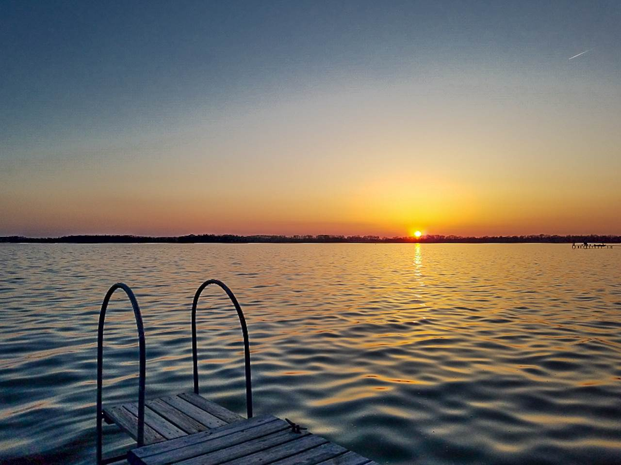Imagine warm summer nights sitting on the edge of the pier, feet dangling in the cool Lake Waubesa waters while watching the brilliant colors of the sunset unfold before you. Ahhhh. What a wonderful, peaceful place to be! This sprawling 4 bed/3 bath home enjoys beautiful views year-round. Winter sunsets can be enjoyed from the cozy living room while basking in the warmth of the wood burning fireplace. The main floor also includes a large office/flex room, formal dining room, large kitchen w/ all new appliances, and laundry. The serene upper level has a large family/rec room and four bedrooms, including the spacious primary suite with lake views, a large bath w/jetted tub, + walk-in closet. Pier and boat lift included.