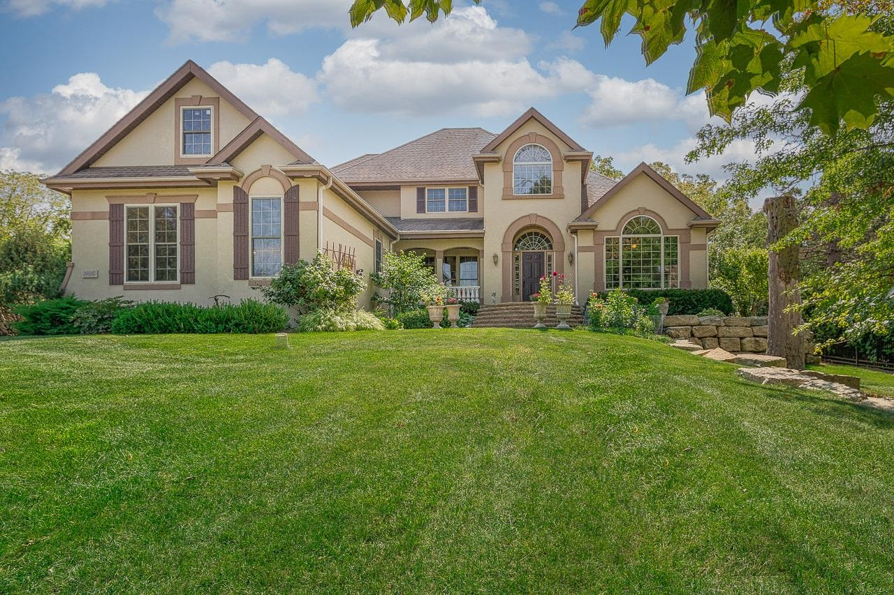 This gorgeous Harlan Hills home perched on a lush green lot w/fenced back yard exudes European elegance w/details like arched doorways, travertine floors, chandeliers dripping w/Austrian crystals, transom windows, & extraordinary private, outdoor spaces. The main level features a great room w/a one-of-a-kind floor-to-ceiling fireplace & walls of windows, a sophisticated dining rm, a private office/den w/gorgeous built-ins + fireplace, & chef's kitchen w/dinette & high-end appliances. A loft overlooking it all makes a great office. The finished LL adds more living + entertaining space w/a kitchenette, rec room, exercise rm, & 3 bedrooms w/great natural light. The main level primary suite has an envy-inspiring bathrm + walk-in closet. Main floor laundry + a 3-car garage, too.
