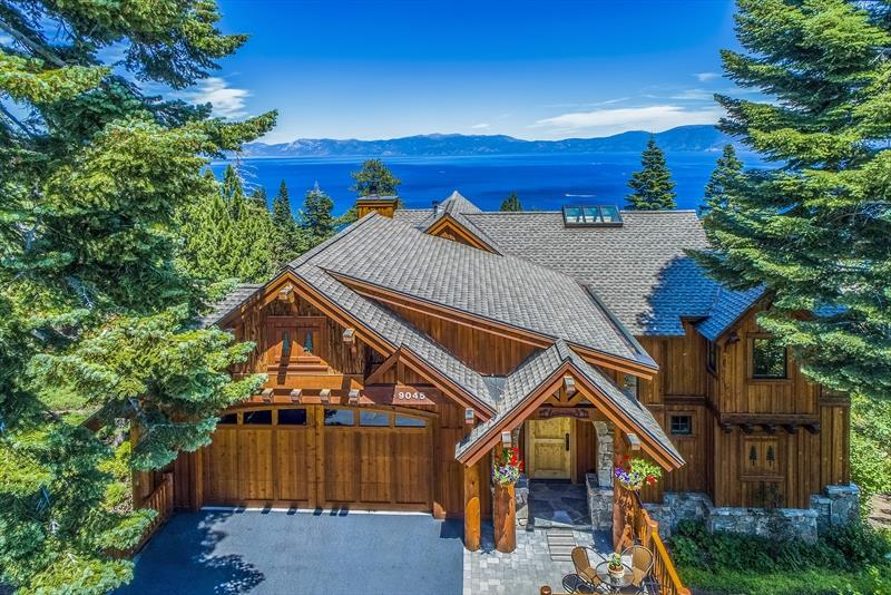 Spacious, open-concept design with 4,107 sf of extraordinary detail and workmanship. This luxurious lodge-style retreat overlooks the pristine turquoise waters of Rubicon Bay with panoramic lake views. Forest service land below allows for unobstructed scenery. Features 4 bedrooms (includes 2 master suites), 3.5 baths with natural stone, 2-car garage and a bonus 700 +- square foot recreation room with separate entry. Tranquil viewing spots with 3 decks, private balconies, and landscaped grounds.